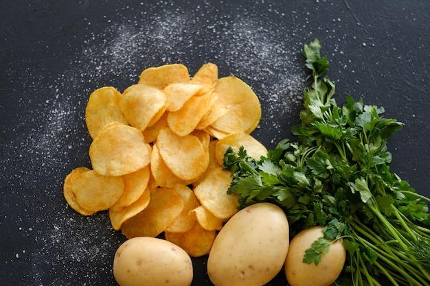 수제 천연 튀김 칩. 매운 칩 스낵과 녹색 허브를 곁들인 신선한 유기농 감자