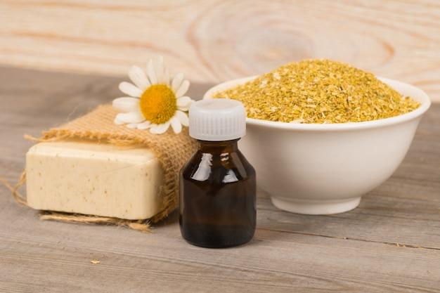 Домашнее натуральное мыло и органическое масло с цветками ромашки и сухими ингредиентами