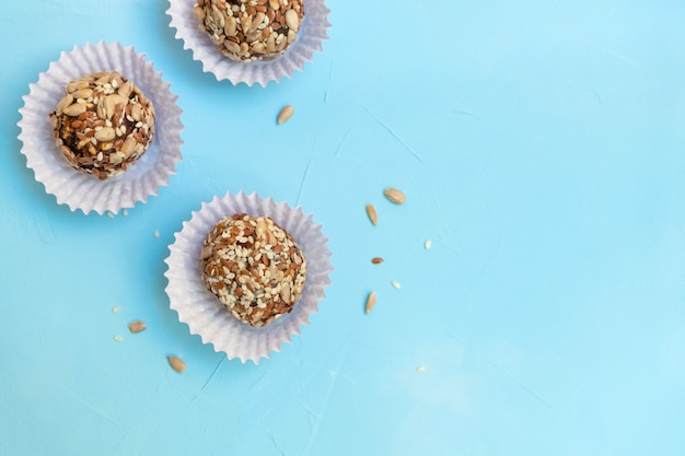 Homemade natural sweets energy balls on pastel blue table.