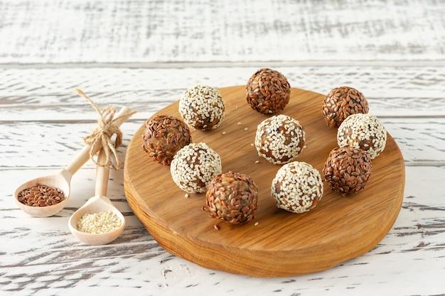 흰색 바탕에 나무 책상에 카카오와 코코넛 플레이크를 곁들인 홈메이드 천연 채식주의 초콜릿 트러플.