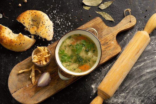 チップス、玉ねぎ、トルティーヤの自家製ヌードルスープ。黒いテーブルの上にスープ、トルティーヤ、めん棒、材料のボウル。上面図。