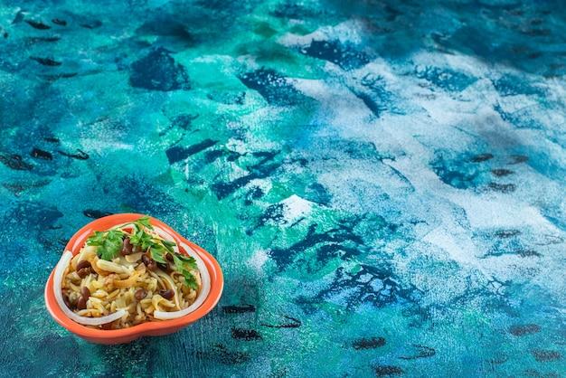 파란색 배경에 그릇에 콩으로 만든 국수.