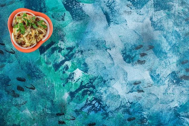 青いテーブルの上に、ボウルに豆を入れた自家製麺。