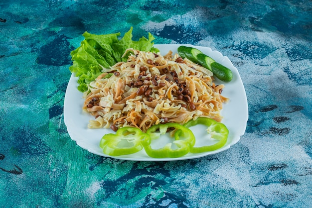 Homemade noodle with slice pepper on a plate , on the blue background.
