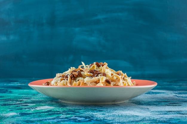 파란색 배경에 삼발이에 접시에 콩으로 만든 국수.