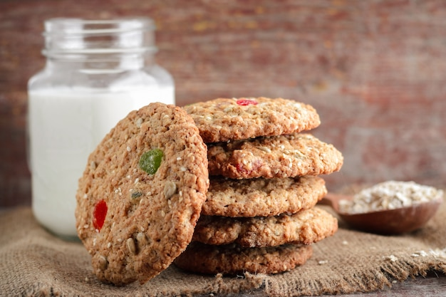 Homemade oat biscuits and glass of milk on a wooden background