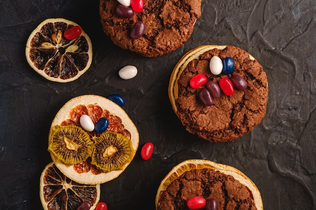 Homemade oat chocolate cookies sandwich with dried citrus fruits and juicy jelly beans on textured dark black background, top view