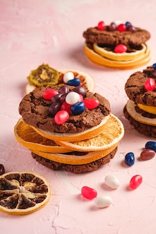 Homemade oat chocolate cookies sandwich with dried citrus fruits and juicy jelly beans on textured pink background, angle view