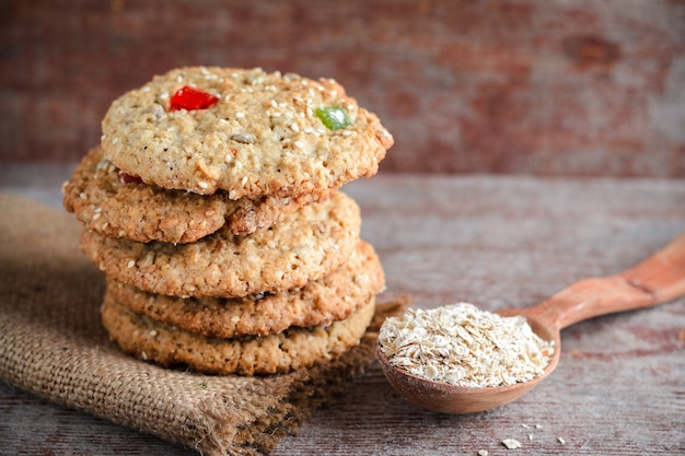 Homemade oat cookies stacked in a pile and a wooden spoon with oat flakes