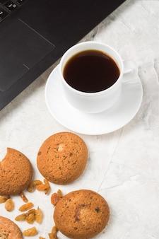 집에서 만든 오트밀 쿠키, 컵 커피와 가벼운 돌 표면에 노트북. 학생 평일