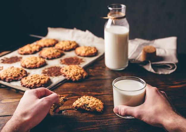 自家製オートミールクッキー。男性の手はクッキーと牛乳のガラスを持っています。背景にボトルと羊皮紙の紙にいくつかのクッキー。