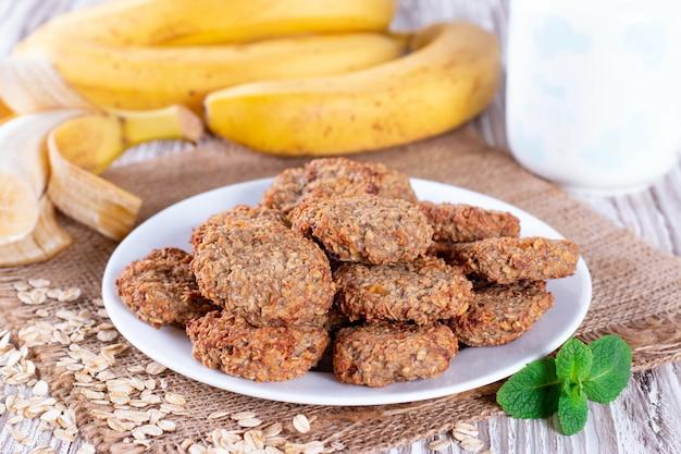 バナナと自家製オートミールクッキー、木製の背景にオート麦。健康的な朝食のコンセプト。