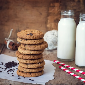 Homemade oatmeal cookies with chocolate and a bottle of milk