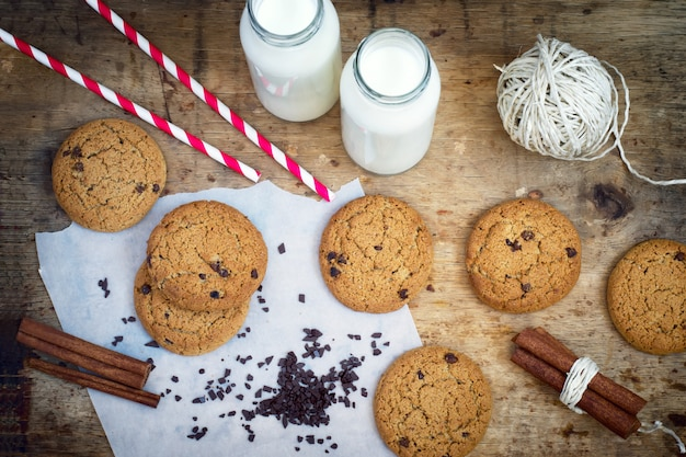 Homemade oatmeal cookies with chocolate and a bottle of milk, to