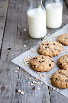Homemade oatmeal cookies with chocolate on an old wooden background.