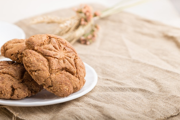 Homemade oatmeal cookies with a cup of cocoa on a white wooden background. side view, selective focus.