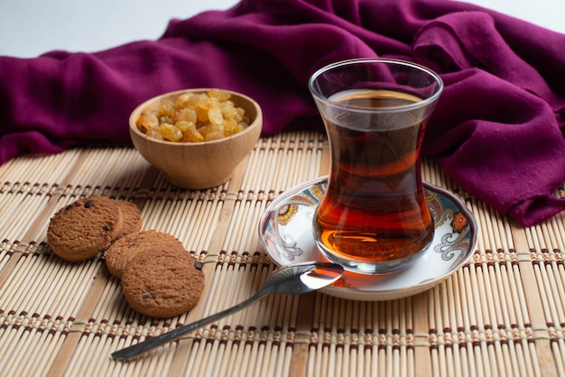 Homemade oatmeal cookies with a cup of tea and a raisin