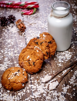Homemade oatmeal cookies with nuts, raisins, candy cane and bottle of milk on dark wooden background