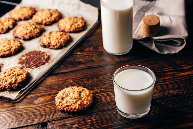 朝食にレーズンとグラスミルクを添えた自家製オートミールクッキー。背景にボトルと羊皮紙の紙にいくつかのクッキー。