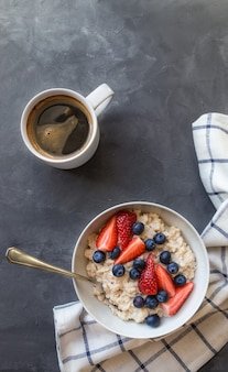 Homemade oatmeal with blueberries and strawberries in bowl on gray concrete background