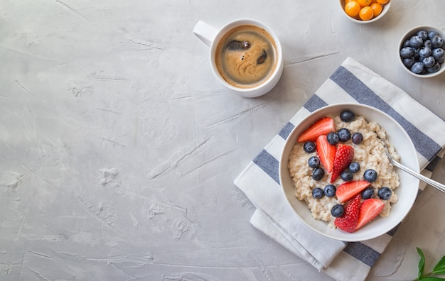 Homemade oatmeal with blueberries and strawberries in bowl on light gray concrete background