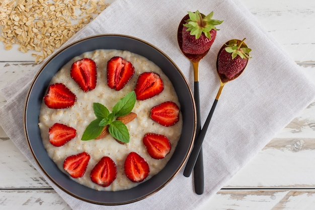 Homemade oatmeal with strawberries in bowl on white wooden background. healthy breakfast. top view.