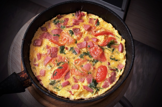 Homemade omelet with tomatoes and sausage in pan. rustic breakfast