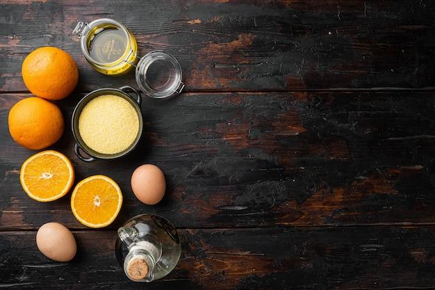 오래된 짙은 나무 테이블 배경에 계란과 꿀이 있는 홈메이드 오렌지 케이크 재료, 텍스트 복사 공간이 있는 평면도