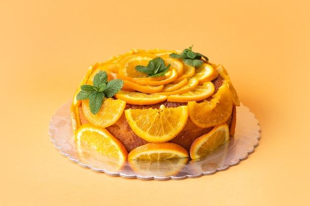 Homemade orange cake with sliced oranges over isolated background