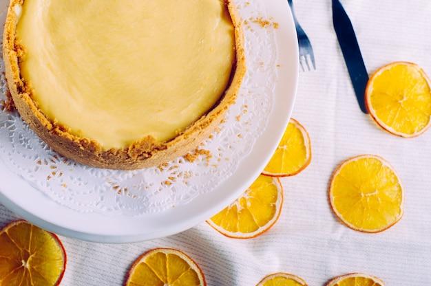 하얀 식탁보에 접시에 수 제 오렌지 치즈 케이크. 평면도, 평면 누워.