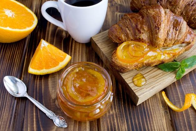 ガラスの瓶、クロワッサン、コーヒーの自家製オレンジマーマレード