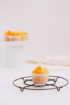 Homemade orange muffins on a metal stand