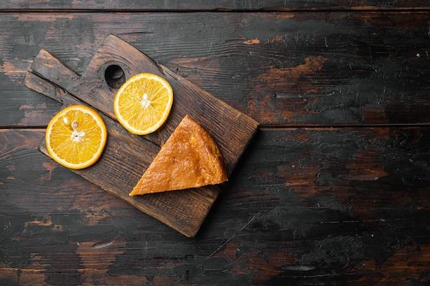 오래된 어두운 나무 테이블 배경에 홈메이드 오렌지 폴렌타와 아몬드 케이크 세트, 텍스트 복사 공간이 있는 평면도