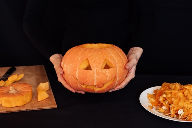 Homemade orange pumpkin for halloween in the hands of a woman