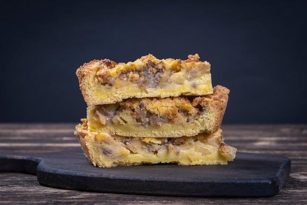 집에서 만든 유기농 사과 파이 디저트를 먹을 수 있습니다. 오래 된 나무 배경에 호두와 애플 타르트를 닫습니다
