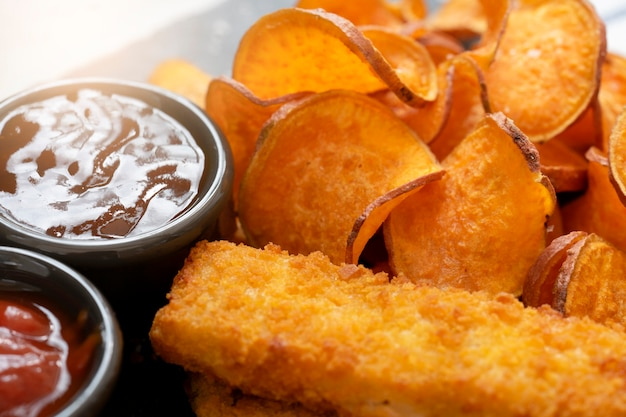 Homemade organic baked fried sweet potatoes chips and fish fingers