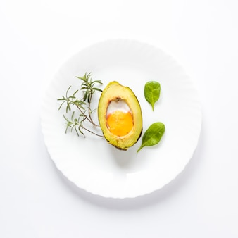 Homemade organic egg baked in avocado with leaves on white background