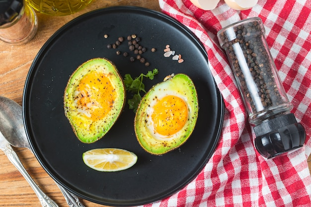 Homemade organic egg baked in avocado with salt and pepper