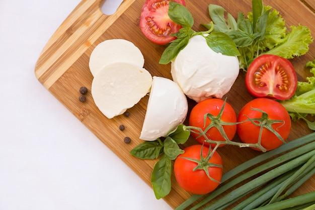 Домашний органический сыр моцарелла с помидорами, базиликом и луком.