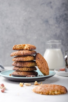 Homemade organic oatmeal cookies with peanuts and jar of milk