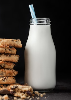 Homemade organic oatmeal cookies with raisins and apricots and bottle of milk on dark wood