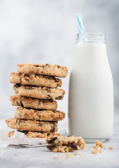 Homemade organic oatmeal cookies with raisins and apricots and bottle of milk on light kitchen