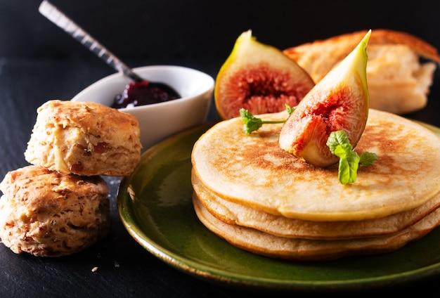 Homemade organic pancakes stack with fig breakfast on black