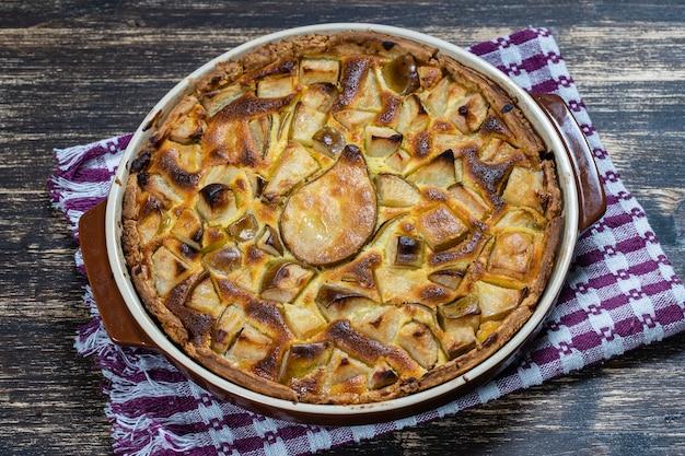 自家製のオーガニック梨パイデザートをすぐに食べられます。古い木製の背景に梨のタルト、クローズアップ。グルテンフリークラストの美しいオーガニックフレッシュフルーツタルト