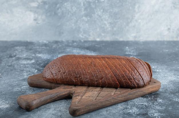 自家製の有機パンパーニッケルライ麦パンをまな板の上でスライスします。高品質の写真