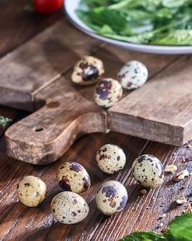 수제 유기농 메추라기 달걀, 접시에 허브와 나무 테이블에 호두 조각. 건강한 샐러드 재료