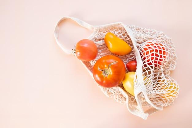 Домашние органические помидоры в авоське на персиковом фоне.