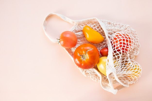 Homemade organic tomatoes in a string bag on a peach background.