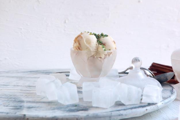 Домашнее органическое белое ванильное мороженое с орехами, кубиками льда и большой корицей