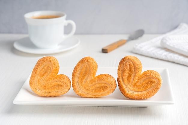 Домашнее пальмовое печенье с десертом, запеченным в сахаре, подается на прямоугольной тарелке с чашкой кофе
